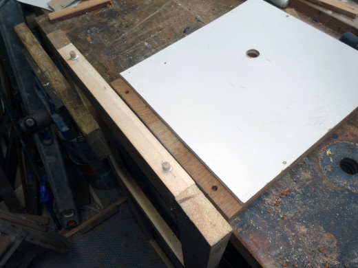 To help hold the front panel tightly in place:  Fitted two dowels, one at each end on the base of the front panel as lugs, and then drilled two corresponding holes in the bottom shelfs to marry up with the lugs.