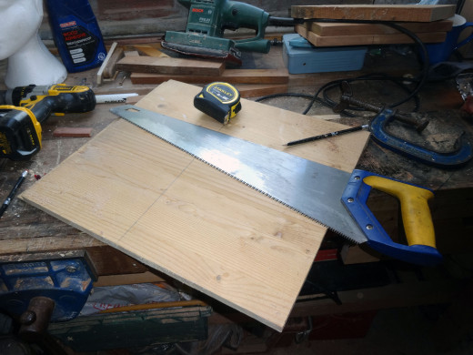 Using the back of a handsaw as a square to mark out the wood, to cut the middle shelves to size.
