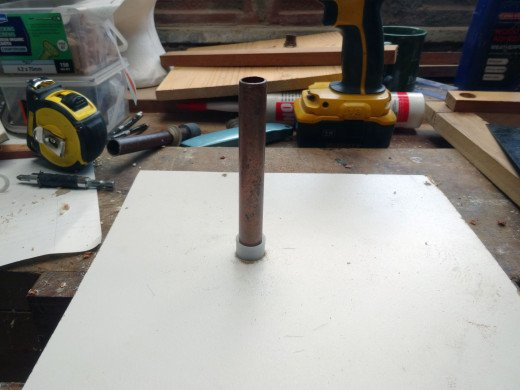 Copper pipe test fitted, held firmly in place with a spare plastic plumbing cap end.
