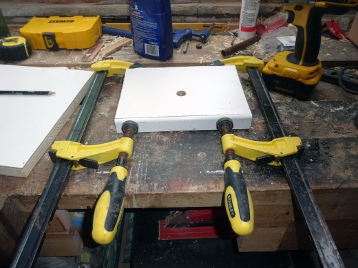Gluing the uPVC trim to the front edge of the shelf, clamping it in place until the glue dries.