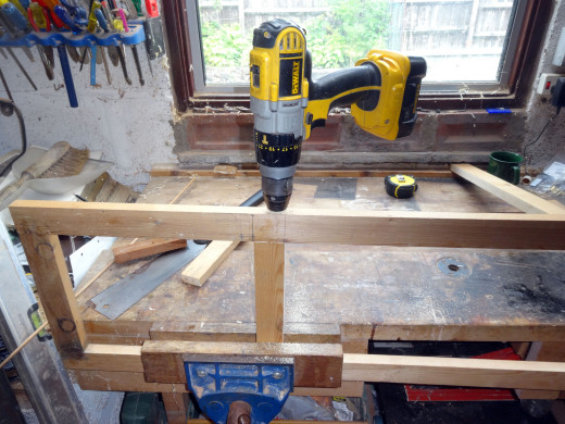Drilling the holes for dowel jointing the new middle rail in place.