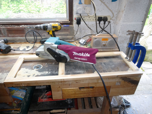 The panel frame is given a quick sanding with a belt sander.