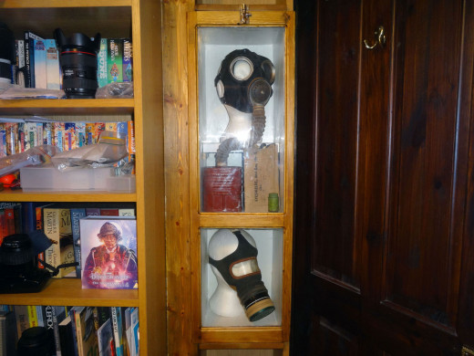 The two gasmasks and other WWII artefacts on display in their display cabinet.