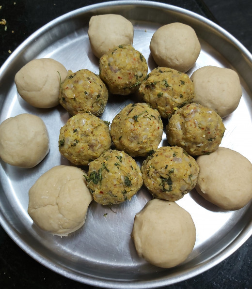 Make equal sized balls from dough. Make same number of balls from lentil mixture also.