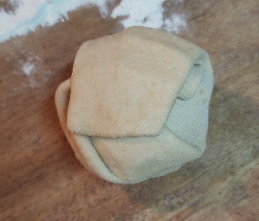 Bring all edges of dough together and seal at the center to make stuffed dough ball.