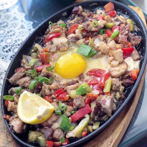 Pork sisig with an egg on top of it. It is usually served on sizzling plate.