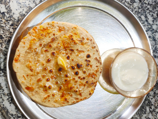 Delicious Gajar-Chhena paratha served with butter and curd