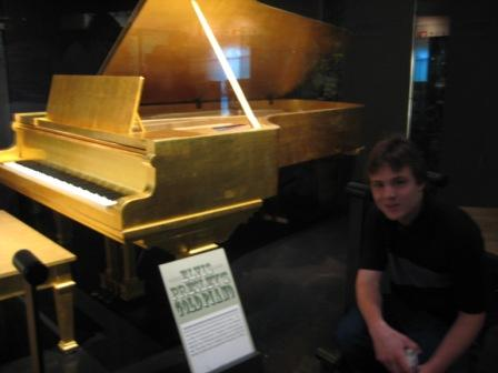 Matthew Schulze in front of Elvis' gold piano at the Country Music Hall Of Fame. Oh, how I wanted to play it!