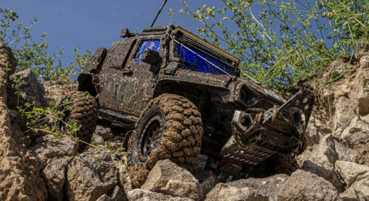 A radio control jeep wheeling over large boulders.