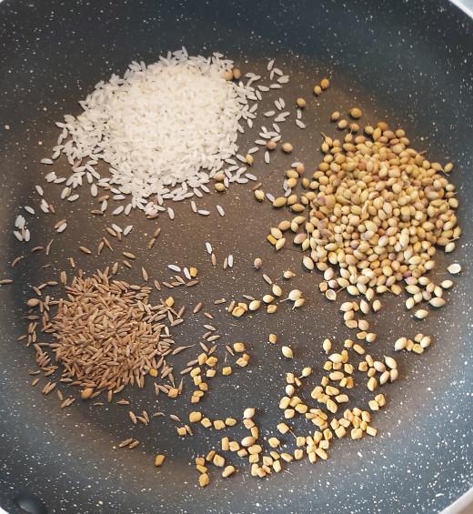 In a frying pan add 1/4 teaspoon of fenugreek or methi seeds, 2 teaspoons of coriander seeds, 1 teaspoon of cumin seeds and 2 teaspoons of white rice (sonamasoori or dosa rice).
