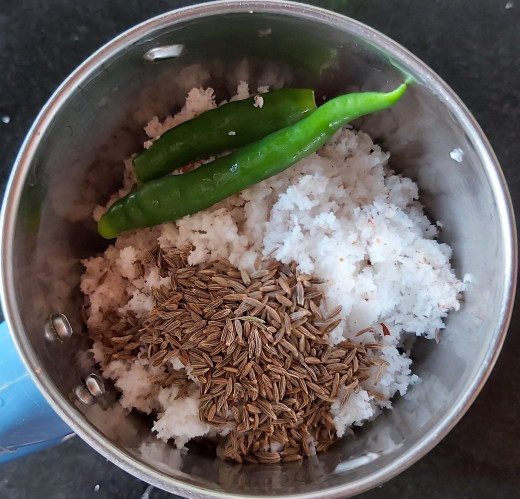 Transfer grated coconut to a mixer jar, add 1 teaspoon of cumin seeds and 1-2 green chilies.