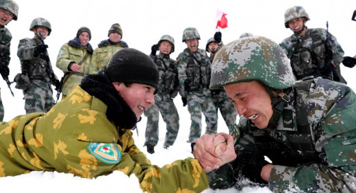 Chinese and Tajik soldiers arm wrestle during patrols near the city of Kashgar, in the northwestern autonomous region of Xinjiang, in May 2019