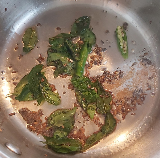 Add 1-2 strings of fresh curry leaves, 1/4 teaspoon of hing or asafoetida and 1-2 split or chopped green chilies (adjust as per taste). Fry fro a minute.