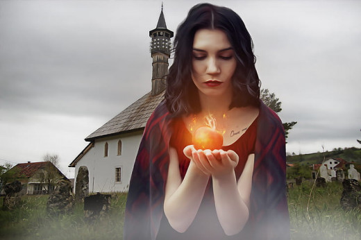 Woman wearing red top and holding apple with fire during daytime