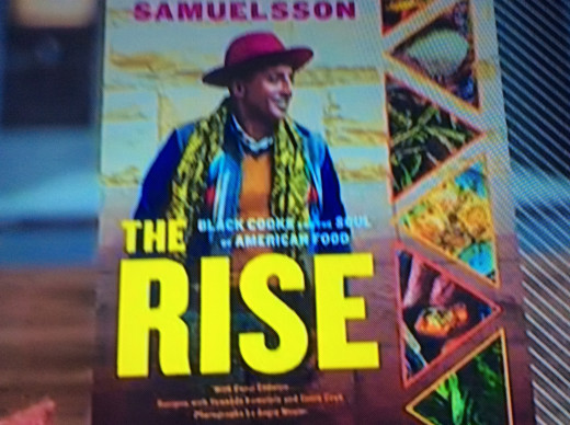 """A photo of Marcus Samuelsson's new recipe book called """"The Rise."""" It discusses the history and origin of black people cooking throughout American history."""