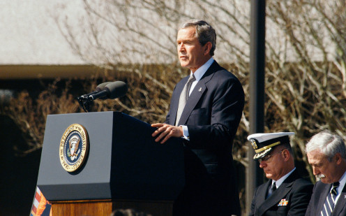 Former US President George W. Bush behind the lectern on an afternoon.