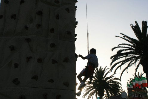 The sun is setting as he is repelling downward from the Rock Wall, note the tops of the Palm Trees as he passes them!  He went pretty high!