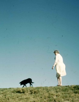 My mother walking our dog Lucky on the hillside