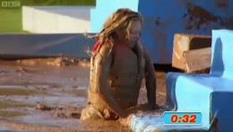 A contestant struggles to get out of the mud