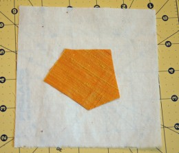 Foundation square with first piece of fancy fabric