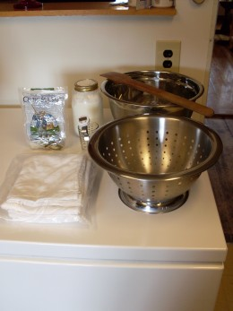 Basic supplies needed to make feta cheese - a large bowl and collander, a long spoon, large cotton tea towels, non-iodized salt, and yogurt or cultured buttermilk. Not shown is liquid vegetable rennet.