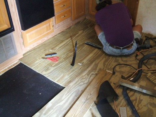 Attaching the new plywood flooring with screws.