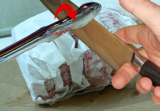 keeping your fingers and small pets well out of the way, TAP the back of the chefs knife with the handle of a butter knife or something similar. The chefs knife will safely work it's way between the burgers, separating them!