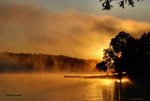 A September sunrise on foggy Upper Hamlin Lake near Ludington, Michigan.