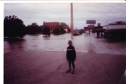 My son, Devin, next to City Lake in Rocky Mount, NC after Hurricane Floyd in September, 1999.  Cannot distinquish between the lake and flooded Sunset Avenue, a main thoroughfare in Rocky Mount.