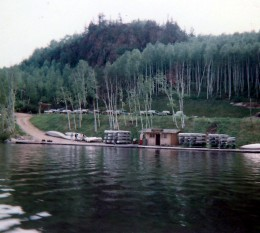 View from a boat on the lake looking back at the Lodge.  See the canoes on the bank of the lake?