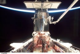 NASA astronaut on shuttle arm working on the Hubble telescope.