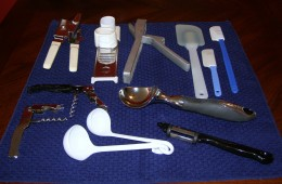 Back L to R; can opener, garlic slicer, garlic press, spatulas; centre L to R cork screws (black handle is step up type), ice cream scoop; foreground; L to R plastic ladles, potato peeler