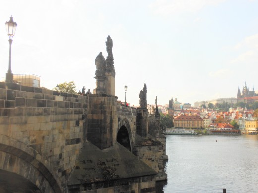 Prague's ancient cultural statues  which survived under uniformal grey Communist rule. The Vltava River flows under the Charles Bridge.