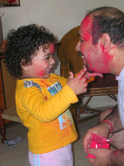 A child and father at home, in colours, on ' Holi Day'.