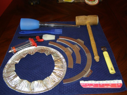 From centre R clockwise: injector, silicone brushes, bulb-top baster, meat mallet, citrus zester, measure tab, aluminum pie plate crust protector; Centre: purchased crust protector.