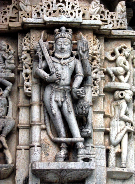 A  ferocious god.Sword in one hand, Head of a man in another.Naked with ornaments dangling on his thighs, he wears a snake on his chest.Wears a moustache and beard. Resembles Hindu god Rudra.