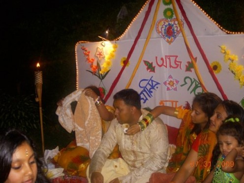 "A Bengali Groom, sitting on the stage with his sister-in-laws on the day of the ""Gaiyer Holud."" The turmeric is already placed on his skin."