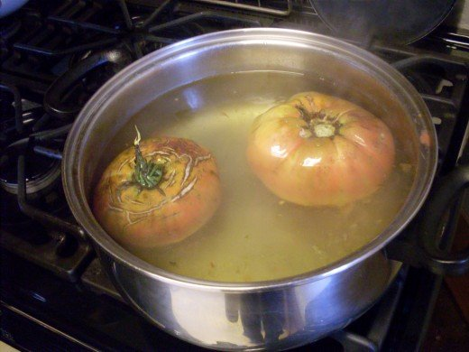 Two large, Caspian Pink tomatoes in simmering water. Not pretty, but very tasty.