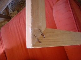 Wood beveled on one side, mitred at 45 and fastened with corrugated fasteners.