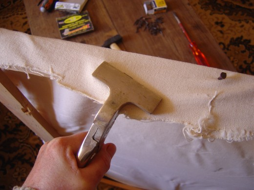 When you have one tack in the centre of each side, start to put a tack about 4 - 5cm on either side of the initial tack. Use the canvas stretchers to tighten the canvas, but also to pull slightly away from the centre.