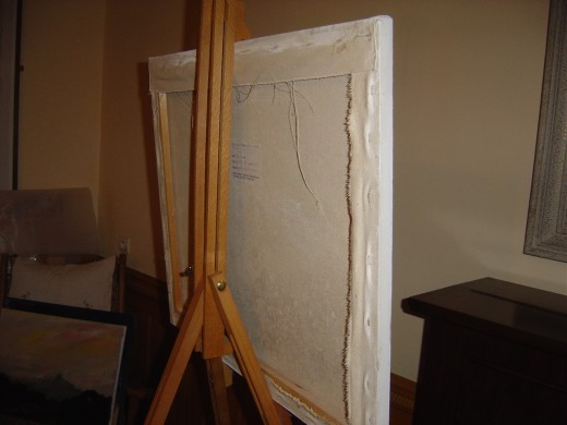 This shows a canvas stretched with staples with corners neatly tucked and secured at the back.
