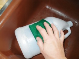 Wash away the excess glue with a scrub pad and then dry the bottle off