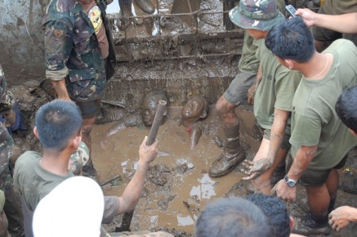 Rescuers stood in silence at the sight of two bodies buried in mud in the aftermath of Typhoon Ketsana