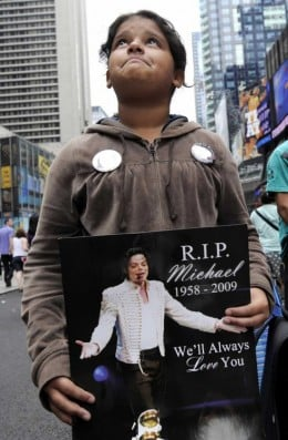 Kayla Moina, 11, of the Bronx, New York, watches television coverage of US singer Michael Jackson's funeral in Times Square in New York, New York, USA on 07 July 2009. Jackson died of a heart attack at age 50 on 25 June 2009 in Los Angeles, Californi