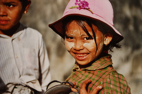 Lucky eyes and beautiful smile of a child in Myanmar. The girl has Tanaka paste in her face. The crust of the Tanaka-Tree is pulverized and touched with water to a paste. This is painted in the face. Tanaka cools and disinfects and protects against t