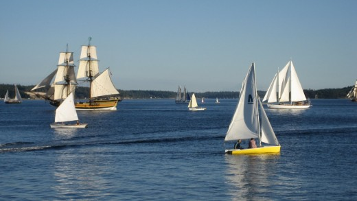 Sailing prams ride schooner and ferry wakes at the Wooden Boat Festival
