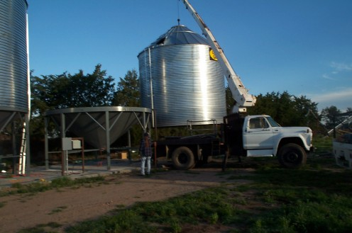 """""""With a boom truck and an operator who is never on time,    We move the bins into place    On the hoppers."""" [These last two bins were new, but at the same location.]"""