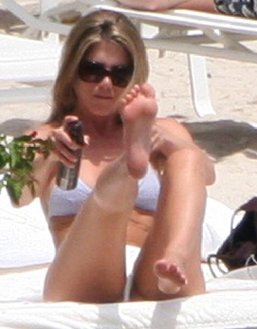 Jennifer Aniston sunbathing and spraying her long legs