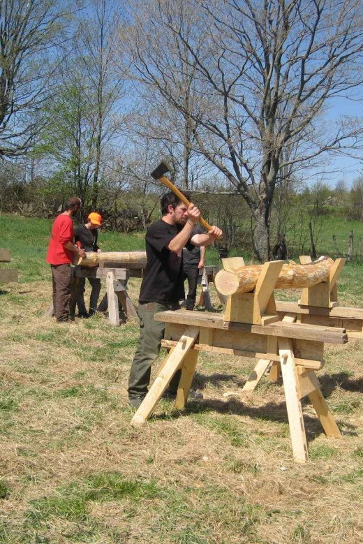 Timber-framing apprentices practicing 'the old way' of squaring off a corner brace (the 'hand-hewn' look goes for a premium nowadays)
