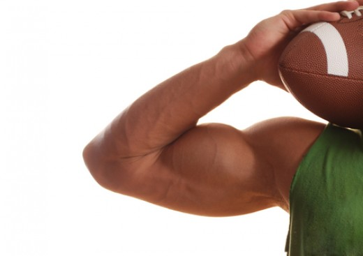 large male bicep muscle with hand holding football